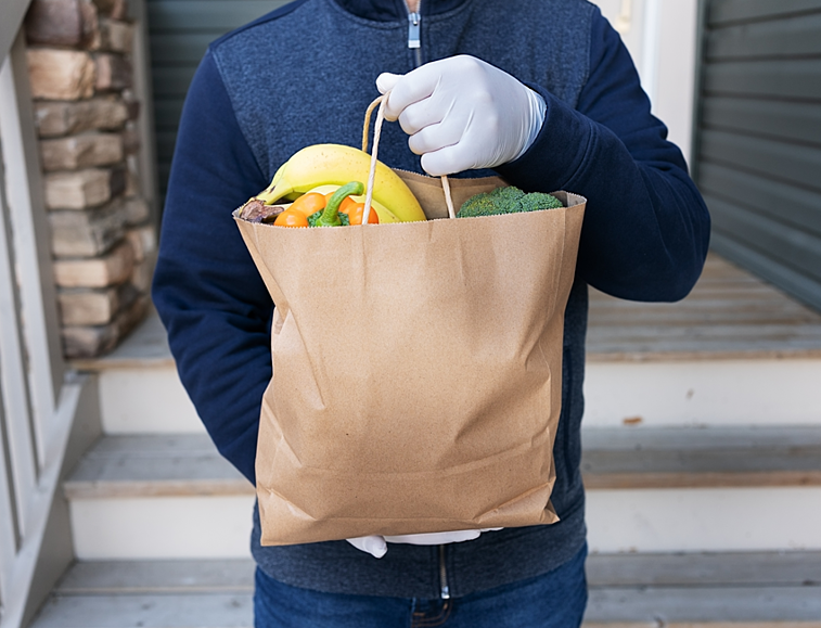 Holding Grocery Bad with Gloved Hands